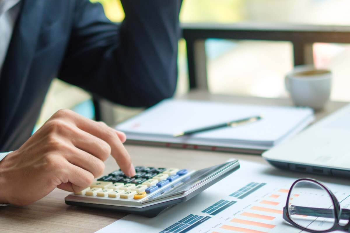 Male restaurant owner sits at table typing on laptop and looks at phone, searching for affordable bookkeeper.