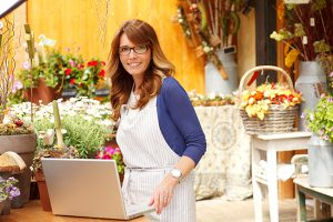 Woman florist smiles in front of laptop in her flower shop.