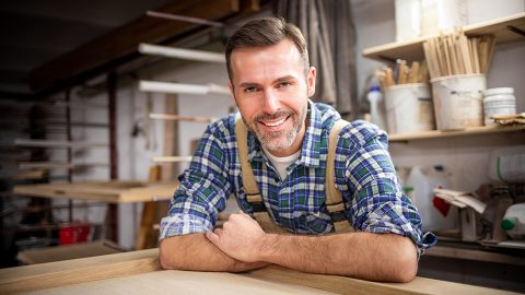 Proud, middle-aged male carpenter leaning on a work table in his workshop, smiling at the camera.