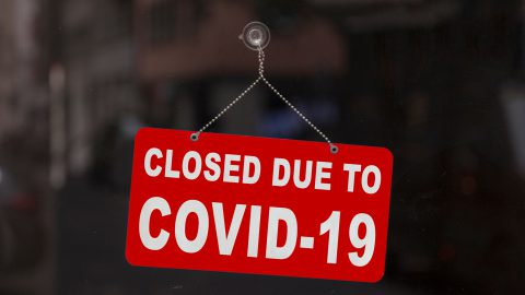 Red and white closed due to COVID-19 sign hanging in a window.