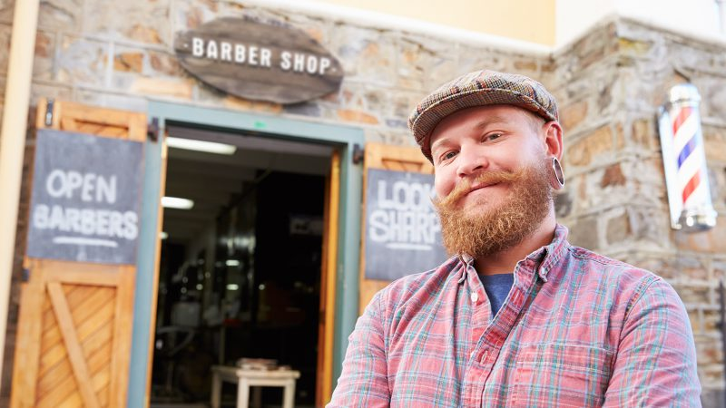Hipster barber is smiling at camera, standing outside of his shoe doors.