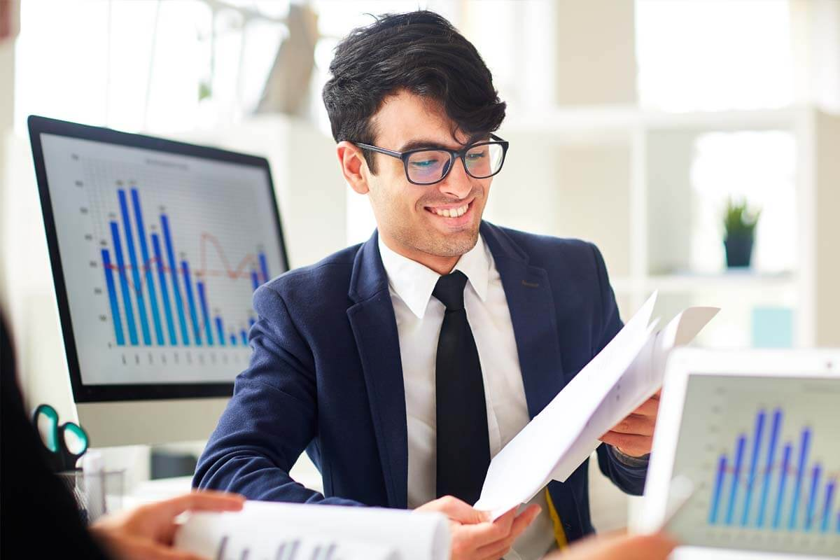 Happy African American baker is smiling and looking at his online account on his laptop.