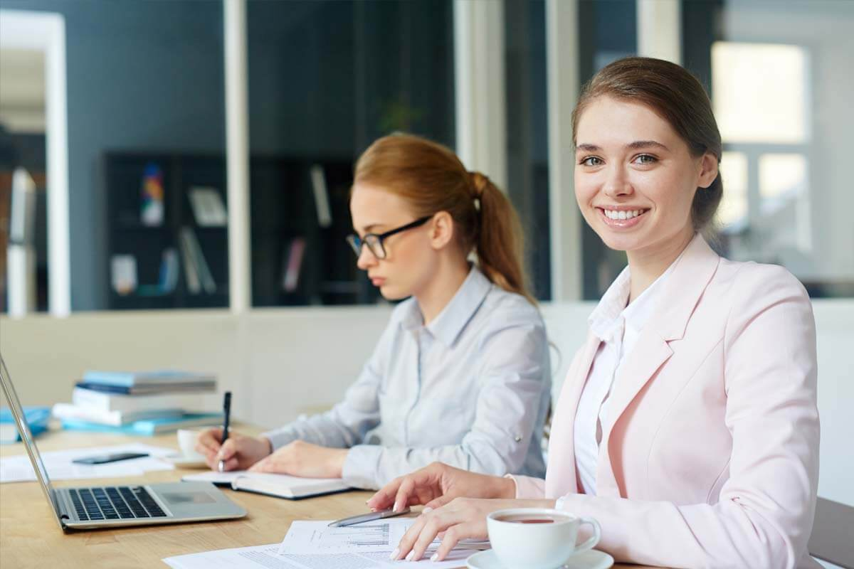 A woman sitting at her laptop with a cup of coffee is working between her calculator and monitor on numbers.